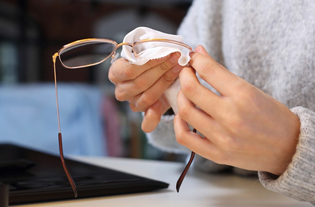 A person wearing a sweater and cleaning glasses with a soft white cloth