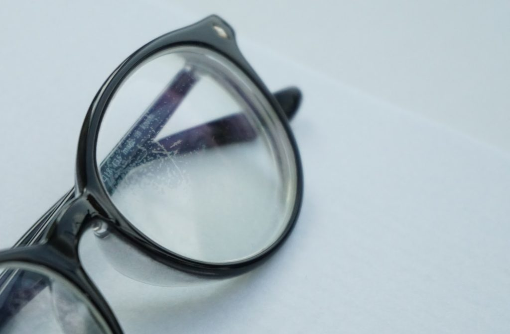 Black pair of glasses on white background with scratched lenses